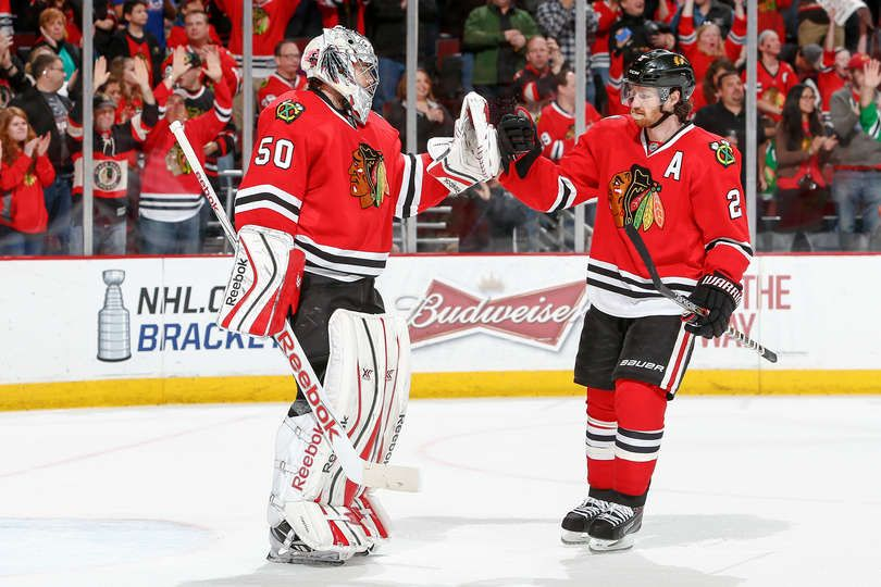 Goalie Corey Crawford #50 celebrates with Duncan Keith #2 after defeating the Vancouver Canucks 3-1 during the NHL game at the United Center on April 2, 2015 in Chicago, Illinois.