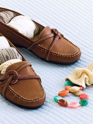 Sock It Away - One way to use every crevice: Slip chunky necklaces and bracelets into socks, then tuck them inside your shoes. Position footwear with soles turned outward, away from your clothes. Flying? Wear your bulkiest shoes on the plane — that'll leave room for that extra set of cute flats or strappy sandals.