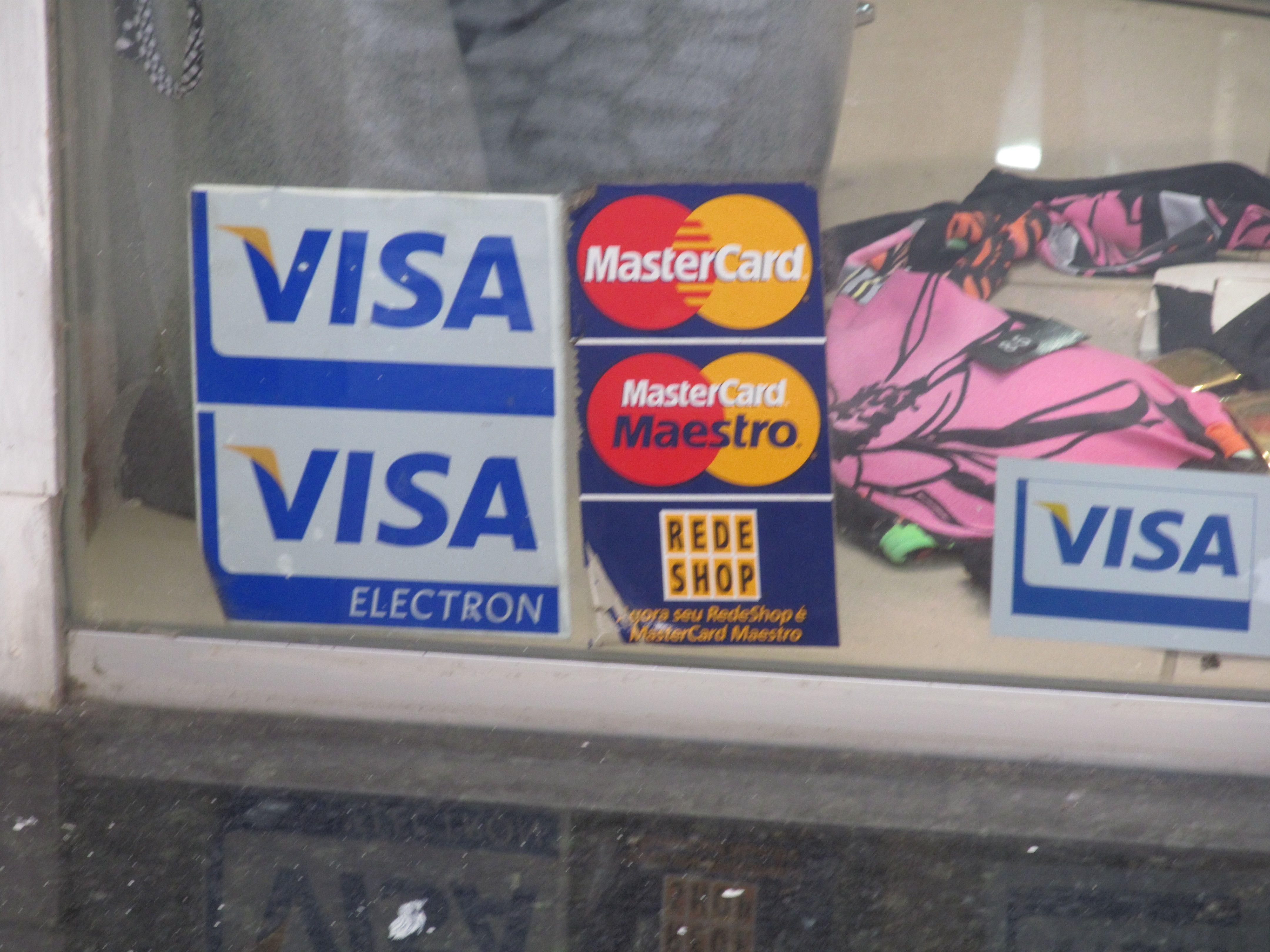 Identidade visual das empresas Visa, MasterCard e Rede Shop, em forma de adesivos afixados a uma vitrine de loja. Os adesivos indicam os cartões aceitos pelo estabelecimento e, portanto, o público a quem se destina a mensagem são os clientes deste local.