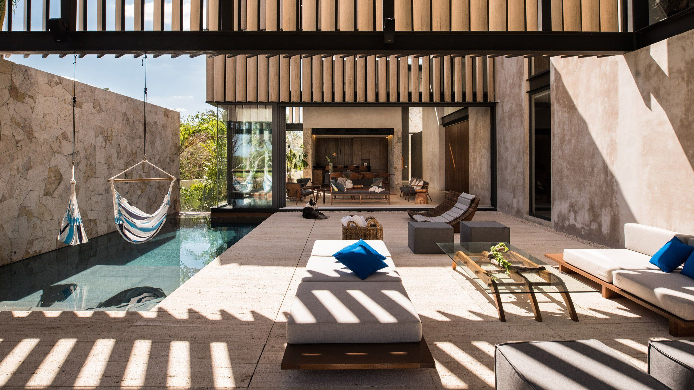 elevated walls with marble slats form a canopy above the terrace and swimming pool of this