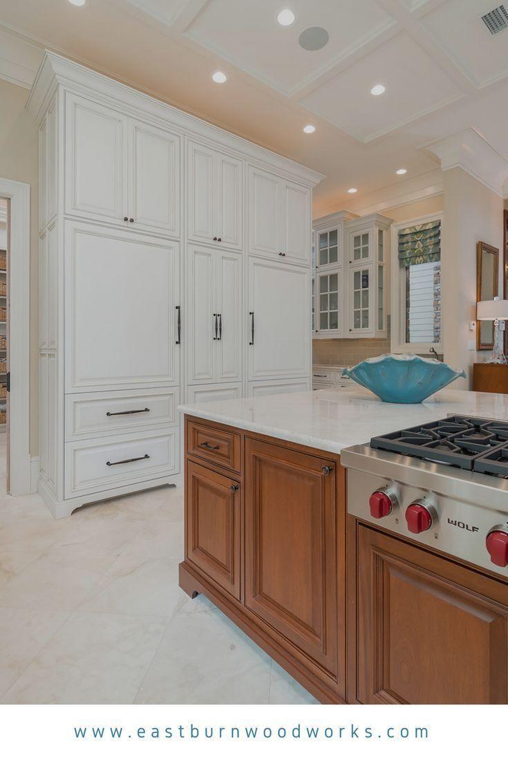 White kitchen cabinetry with decorative raised panels and a stained kitchen island built by ...