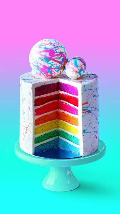 Seven cheerfully colorful rainbow layers are stacked tall with white chocolate spheres on top!