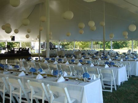 pole tent with paper lantern lighting with banquet tables floor