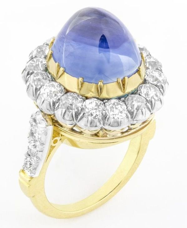 A VICTORIAN SAPPHIRE AND DIAMOND RING ~ The cabochon sapphire centre estimated to weigh 15.00ct in a yellow gold cut-down setting, surrounded by sixteen old brilliant-cut diamonds, in a silver cut-down setting, with diamond set cherniered shoulders, total weight of diamonds approximately 1.90ct.