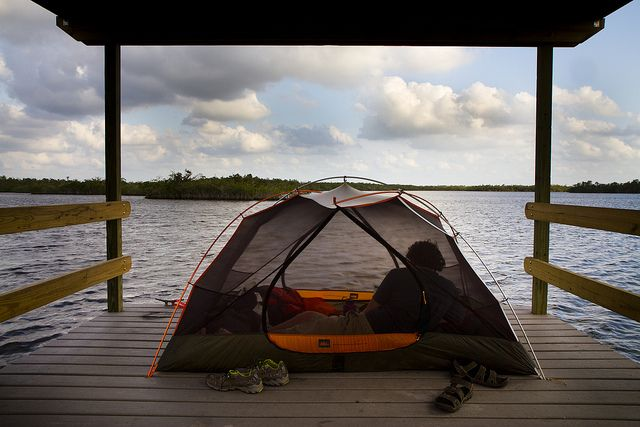 A camper enjoys the view from his tent on one side of the Pearl Bay Chickee.