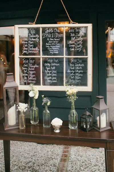 Table under window, but with mix of mason jars and vintage bottles with flowers and votives.
