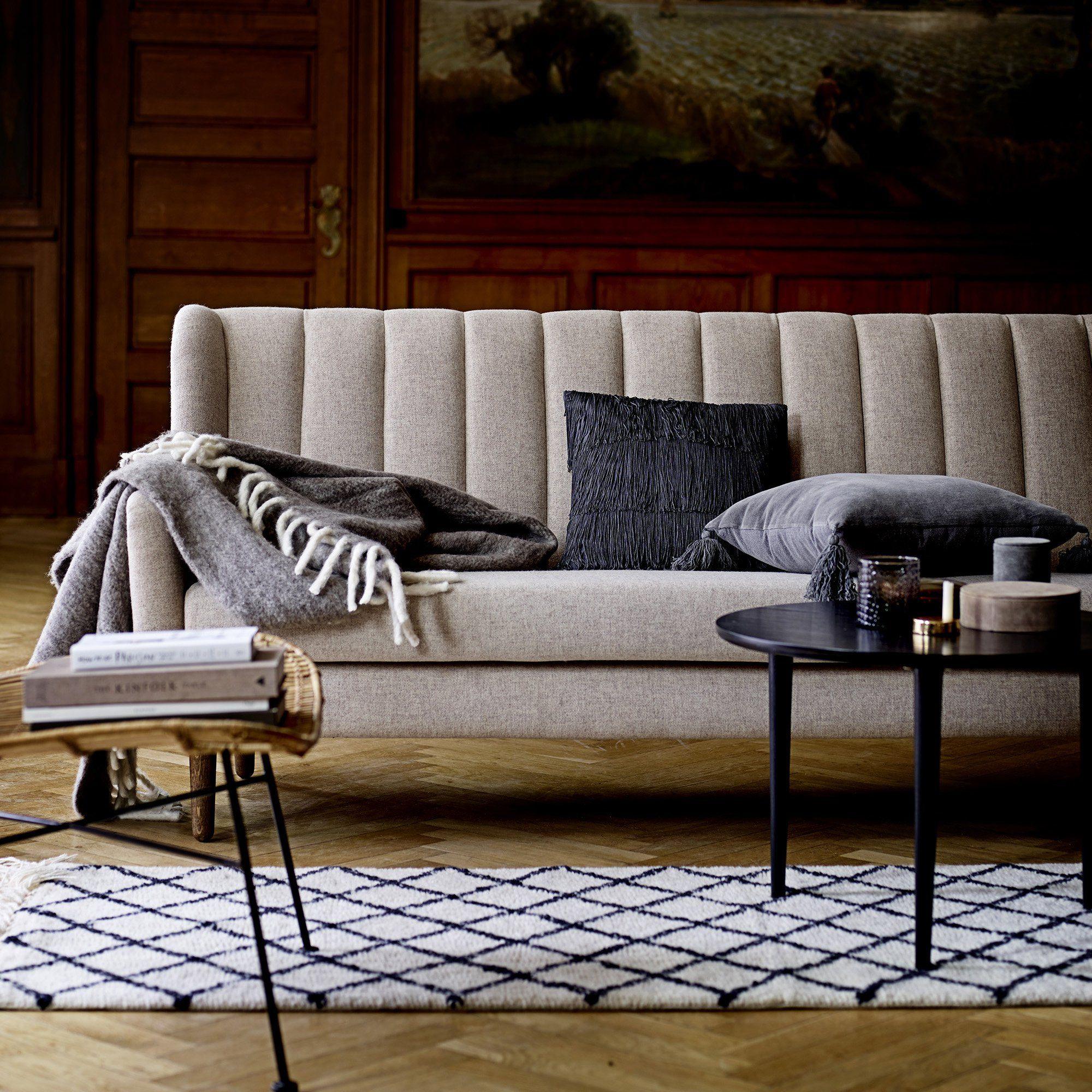 Un canapé greige gris droit et inspiration art déco avec pied en