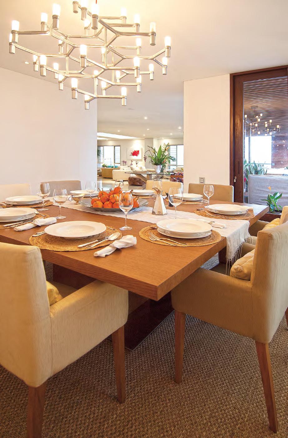 LA LÁMPARA EN ACERO CEPILLADO enmarca el comedor, que ve complementada su mesa de madera con las sillas en seda y algodón, diseño de Ralph Lauren.