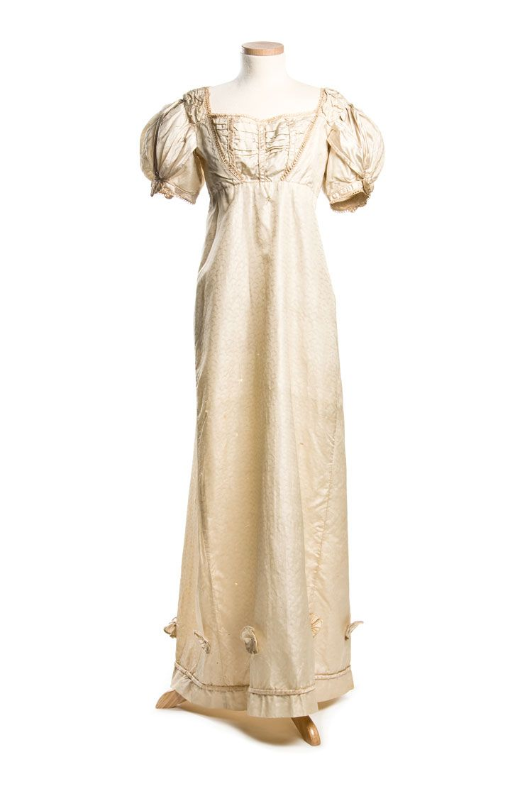 """Wedding Dress: ca. 1803, embossed silk, the neckline and high waistline are fastened in back with drawstrings, the bottom features piping and delicate silk rosettes. """"It may have been worn as a wedding dress by Susannah Richardson (1789-1824) who married John Boyd and was again worn by her daughter, Margaret Ann Boyd Johnson who married her second husband, David St. Pierre DuBose in 1831."""""""