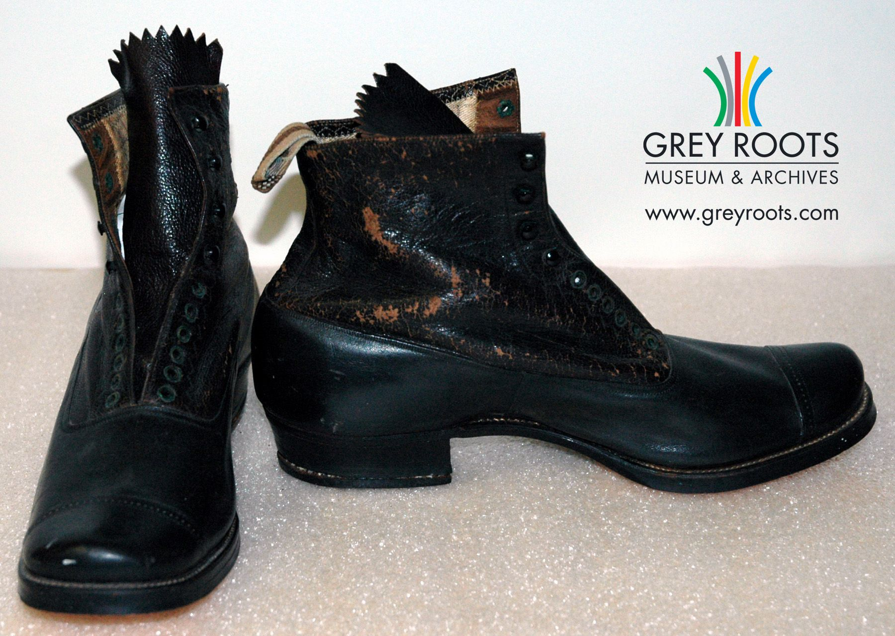 """A pair of men's, black leather boots with leather soles and rounded toes. The boots are lined with a checkered brown and beige cotton lining. The sole is stamped with a trademark that includes the word """"Foward"""". Grey Roots Museum and Archives Collection."""