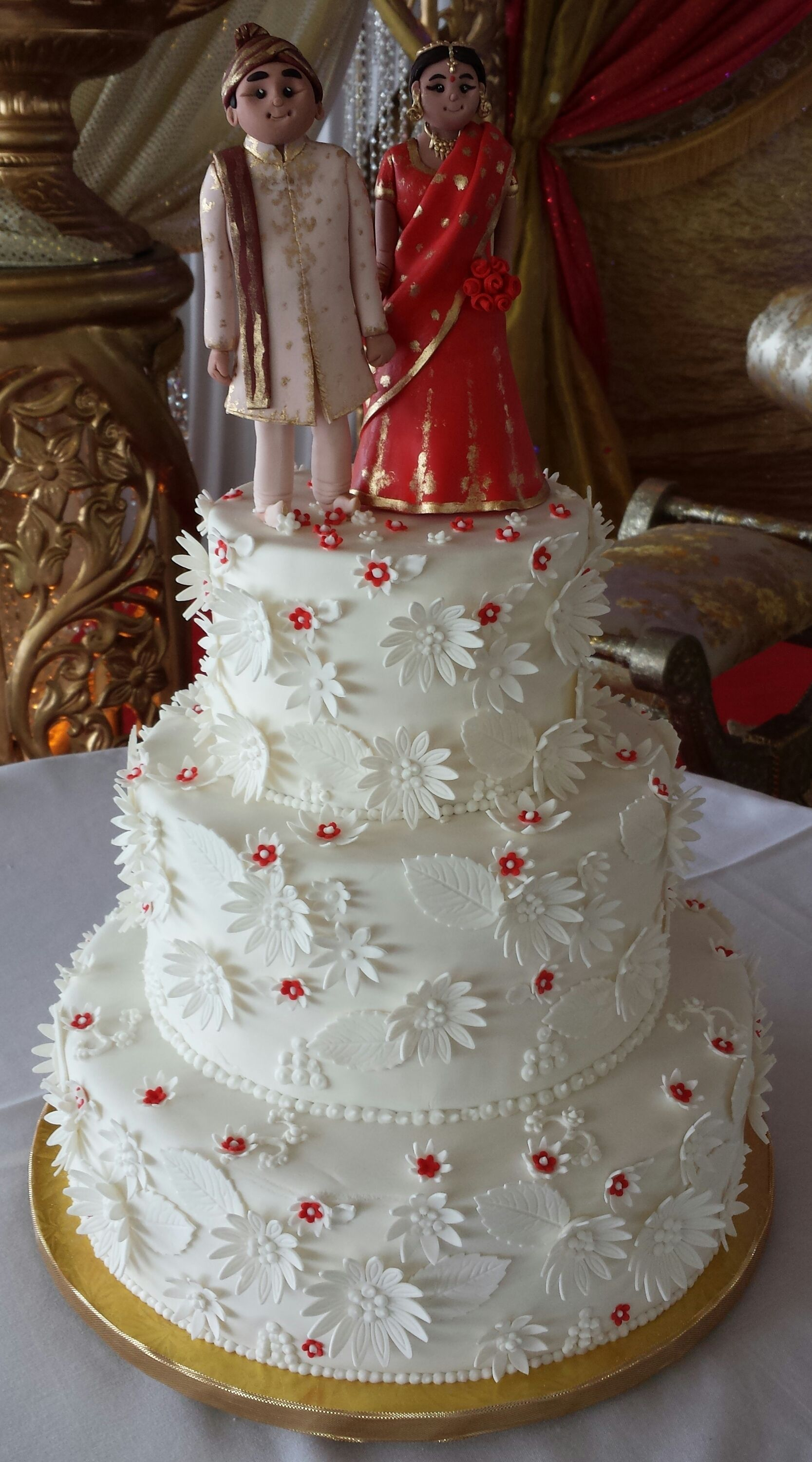 wedding cake for a bangladeshi couple with bride and groom cake topper in traditional wedding costume