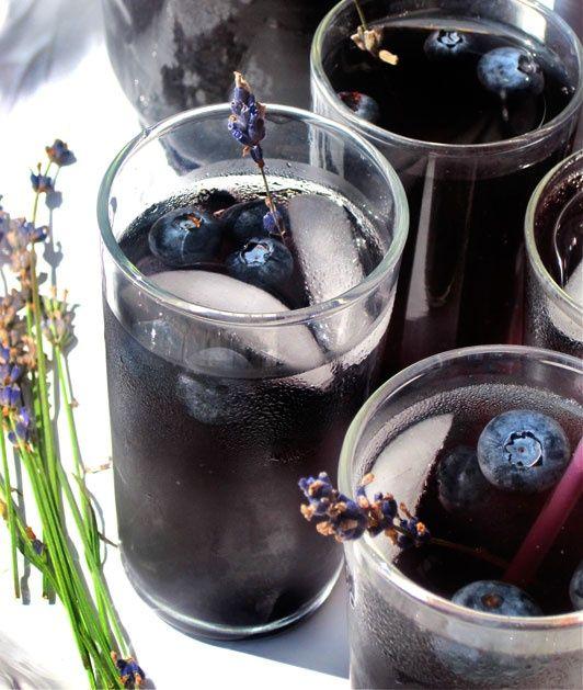 Blueberry Lavender Vodca: Ingredientes: 1 xícara de blueberries para os cubos de gelo, 2 copos de vodca, 3/4 xícara de blueberries, 4 doses de suco de limão, Água com gás e lavanda fresca para enfeitar.  Modo de preparo: Divida a xícara de blueberries entre duas formas de gelo, encha com água e deixe congelar completamente.  Em uma jarra, misture a vodca, suco de limão, o blueberries e a água com gás. Adicione cubos de gelo e sirva com os raminho de lavanda.