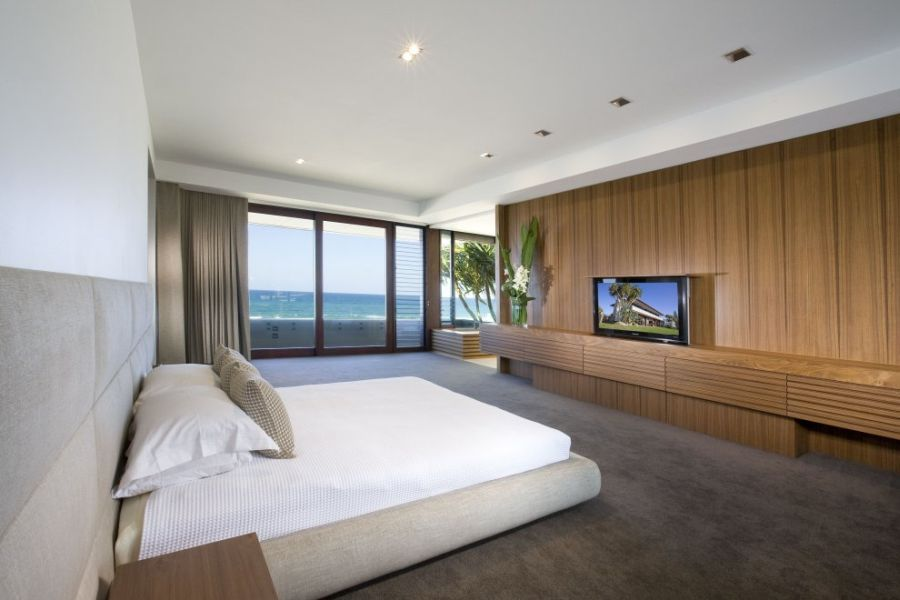 Inspiring contemporary beach house in queensland with luxurious exterior flat screen tv in modern bedroom with white bedding and beach sce