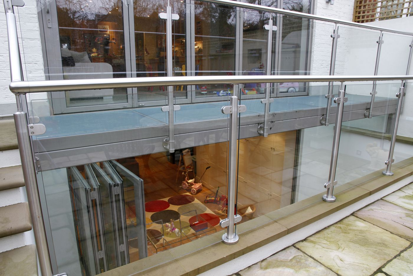 Lightwell With Glass Bridge Above And Steps Up To Garden With Bi - Metal basement doors
