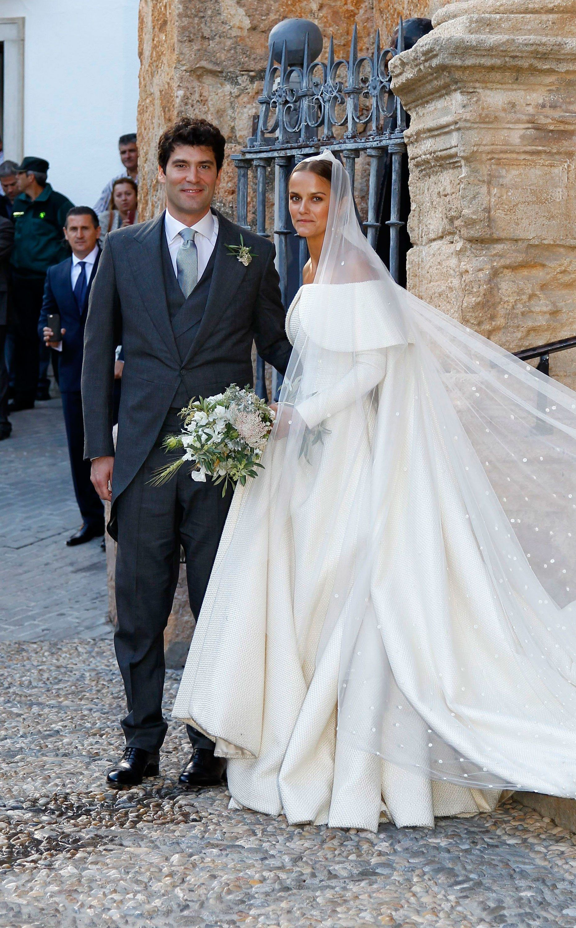 The Bride Wore An Off Shoulder Emilia Wickstead Wedding Dress And A Cathedral Length Veil Accented With Embroidered