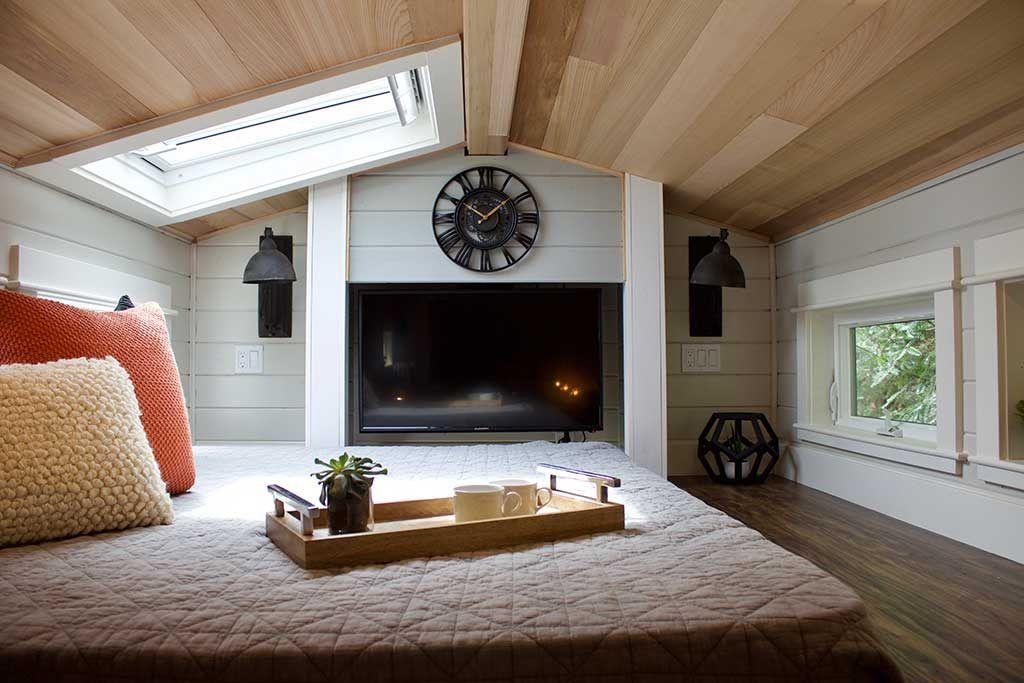 Loft with a beautiful fireplace | TINY HOME, BIG OUTDOORS | Tiny Heirloom Luxury Custom Built Tiny Homes