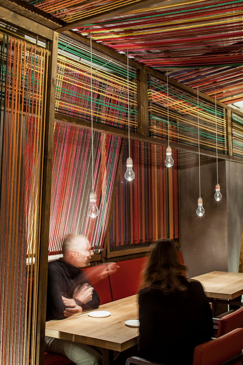 El equipo creativo have designed the pakta restaurant in barcelona spain that features an interior with brightly colored ropes