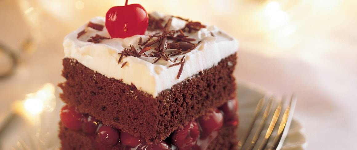 Bake this delicious black forest cake that's filled with cherries and topped with chocolate curls - perfect for dessert.