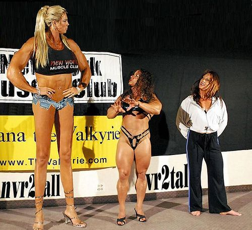 giant blonde talks with some shorter people | Tall women. Giant people. Muscle girls