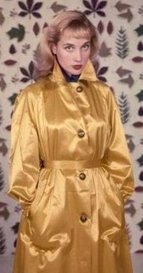 A Young Sylvia Syms In A Gold Rubberised Satin Mac The