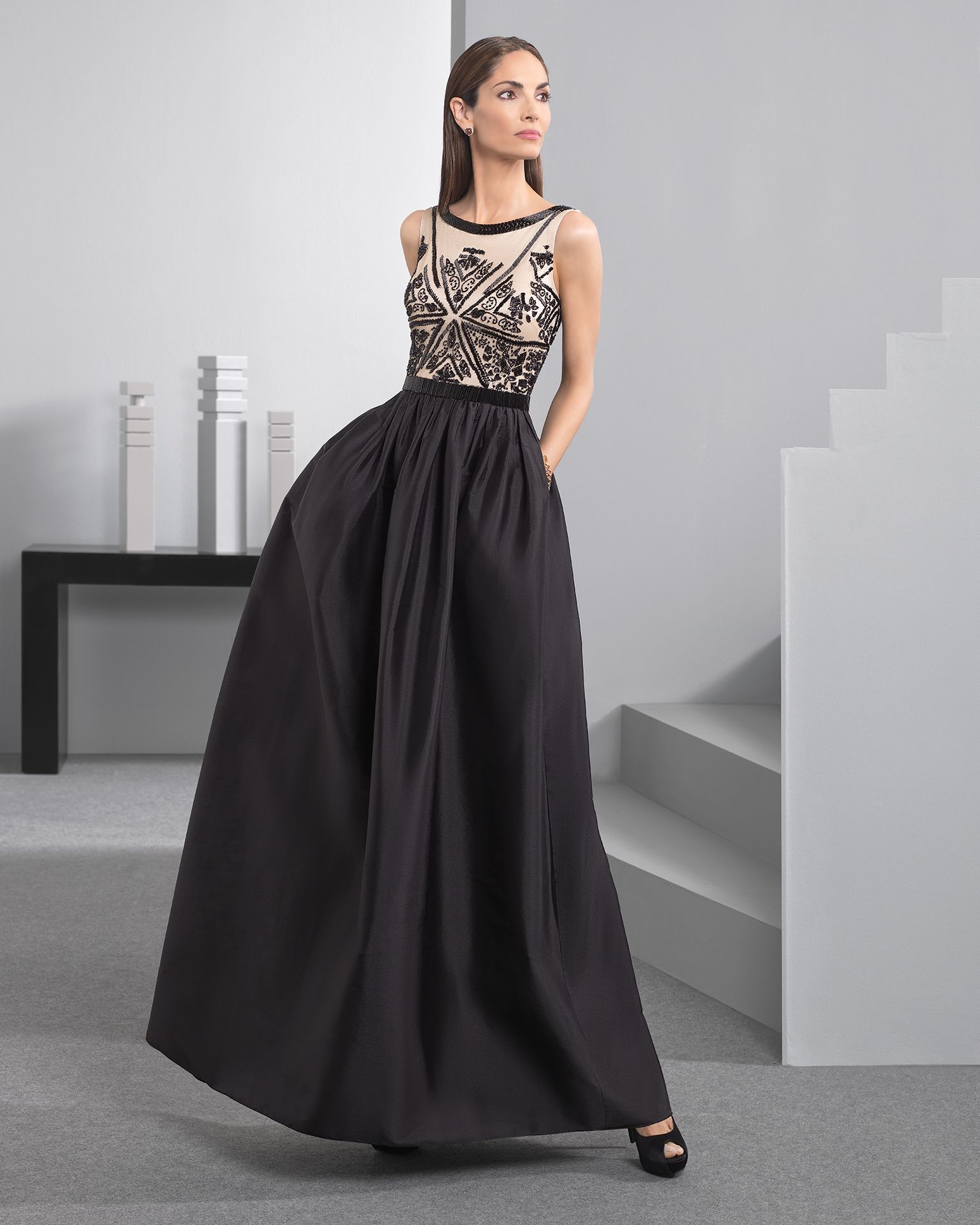 Vestido comprido confecionado com corpo de brilhantes e saia de tafetá, com  gola redonda e costas em bico, complementado com transparência, em  preto cor de ... 82d4bcd882