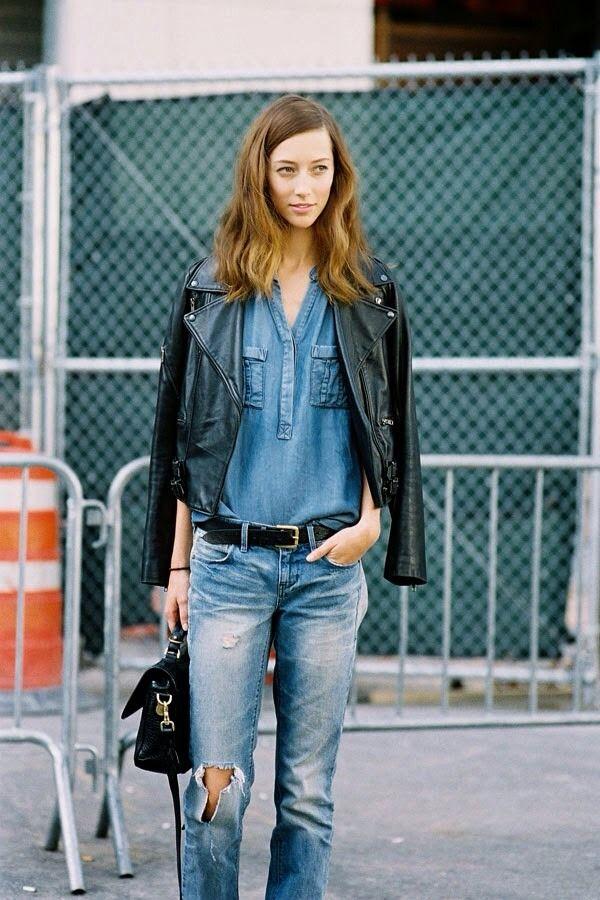 b78429aeb90b Black leather moto jacket draped over the shoulders worn with a chambray  top tucked into ripped jeans Inspiration Jean Louis David