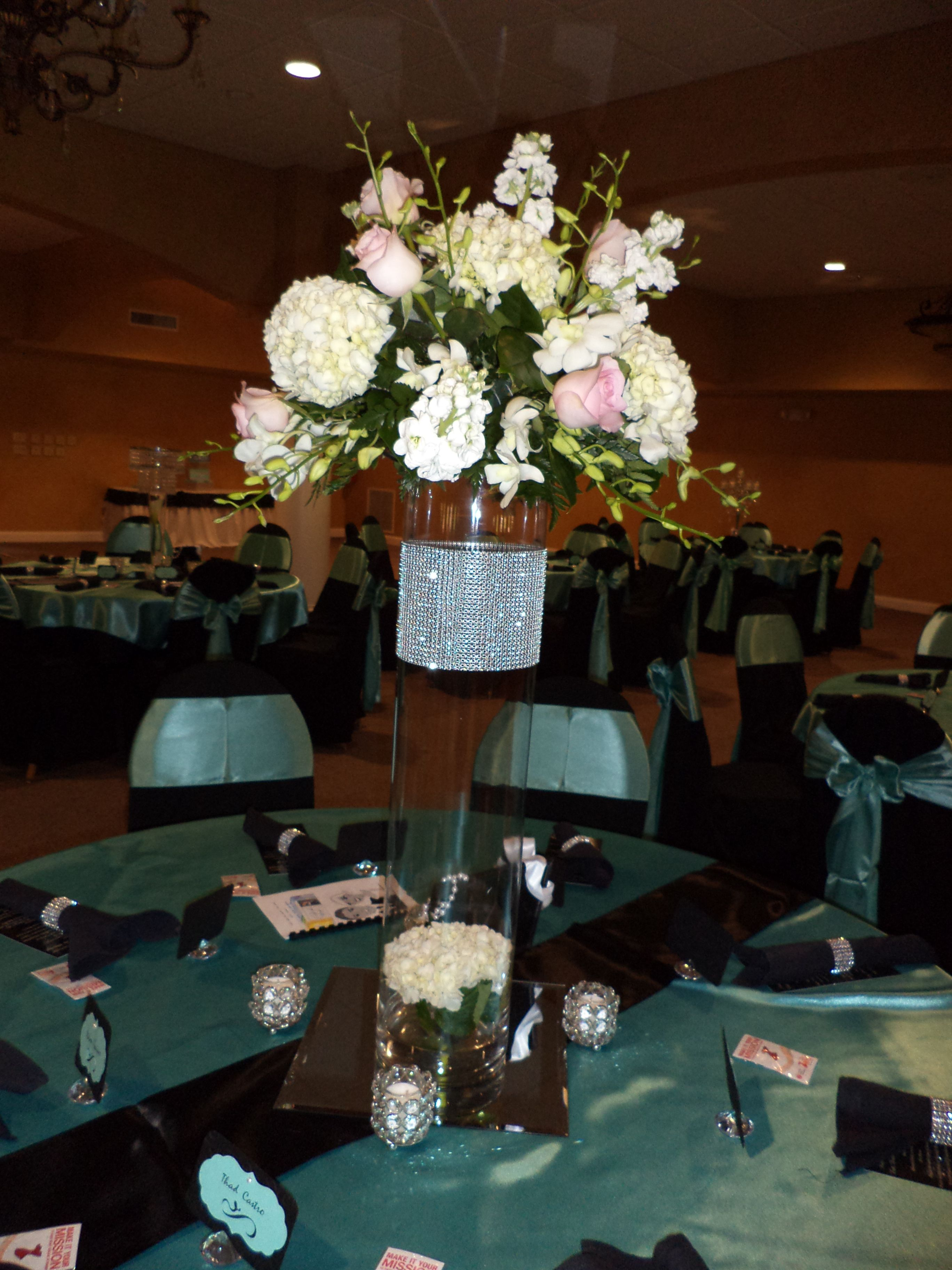 Tall vase style centerpiece, hydrangeas, roses, orchids with a diamond wrap.