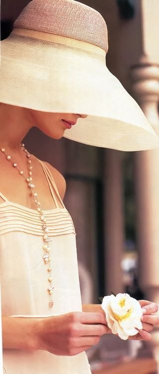 This lady is polished and elegant from her pearls to the little flower she holds.