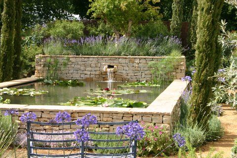 Raised stone pond with dry stone walls and coping stones - award-winning garden by Claudia de Yong Designs, UK.
