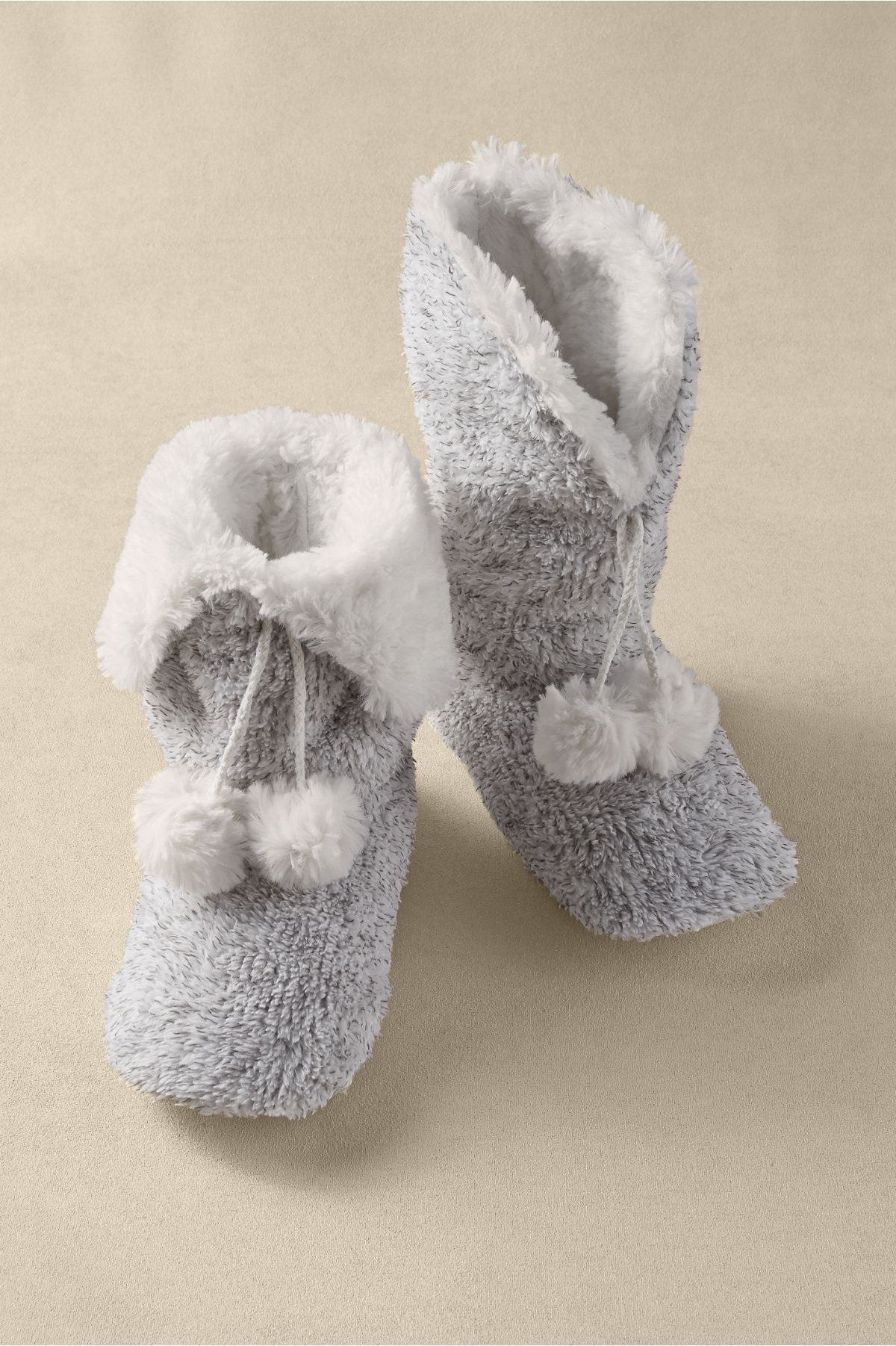 Plush, faux fur lines these soft slipper-booties, hand-knit in textural yarns with pompoms and padded footbed. Skid-free synthetic sole. Poly.