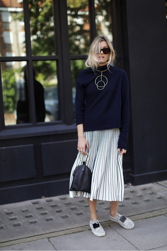 Camille Over the Rainbow wears a turtleneck sweater, pleated midi skirt, printed sneakers, a mixed material bag, statement necklace, and black sunglasses