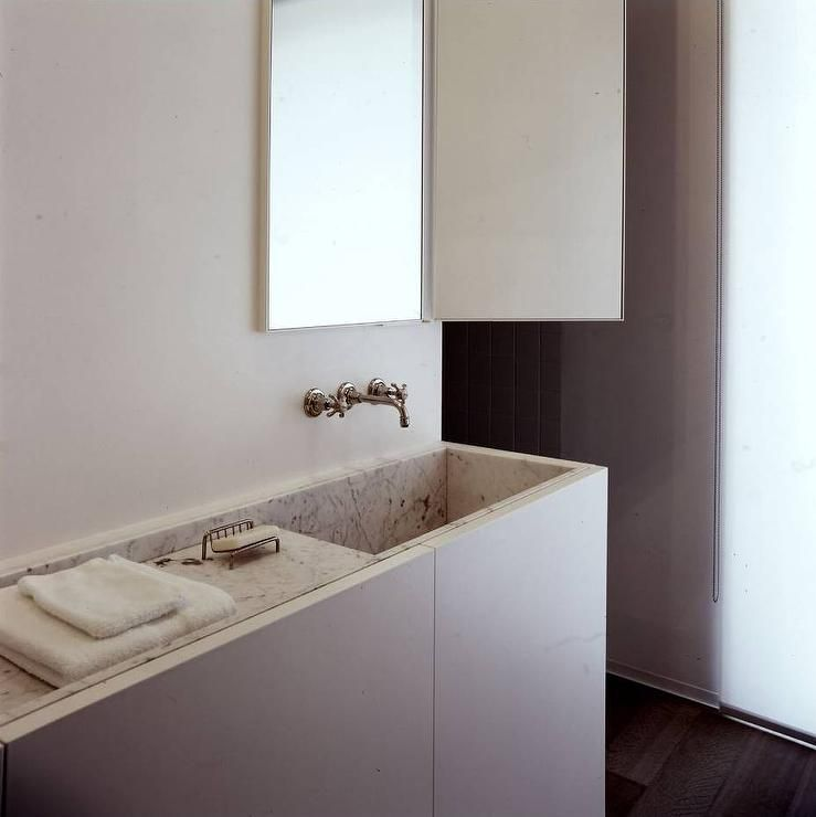 Modern bathroom features a slim washstand fitted with a marble sink ...