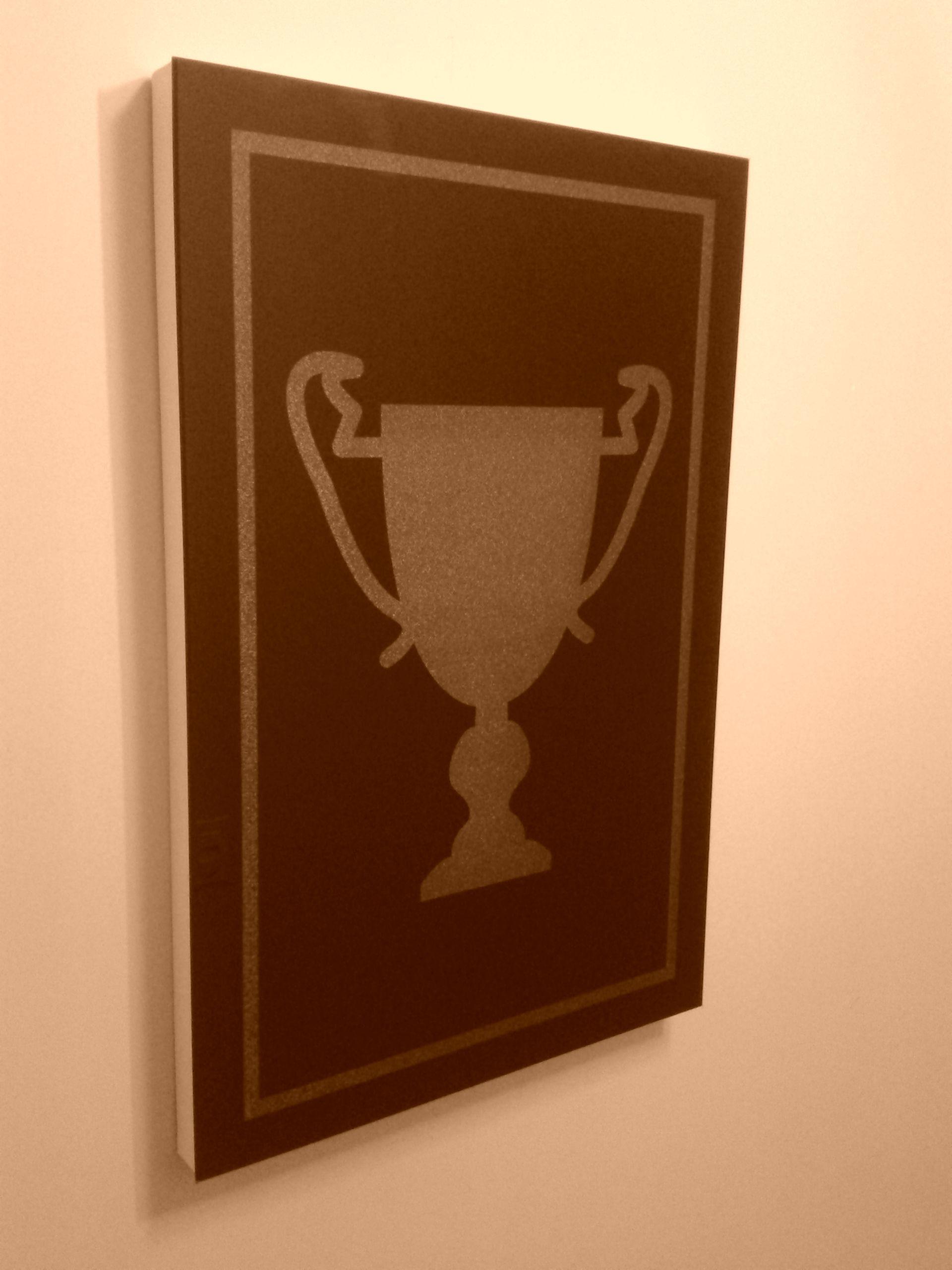 quadro com imagem de troféu, vidro preto, moldura branca. o trabalho foi feito com gravação a laser