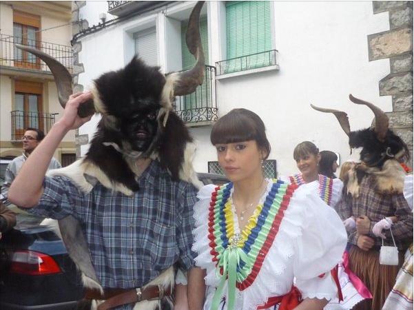 """El Carnaval de Bielas (Huesca): Un grupo de hombres llevan palos largos, faldas, y cencerros. Ellos pintan sus caras de negro. Este grupo se llama Trangas. Bailan alrededor de un hombre que pretende ser un oso, llamado """"l'onso"""". Las Trangas bailan con unas jovenes, llamadas """"mandamás"""". Ellas simbolizan puridad y llevan vestidos coloridos."""