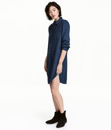 Dark denim blue. CONSCIOUS. Tunic in soft Tencel® lyocell with a chest pocket, collar, and button placket. Long sleeves with buttons at cuffs. Gently