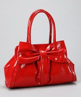 A structured shape is just the thing to partner with a polished ensemble. The sweet bow embellishment pairs with a glossy finish, creating the ultimate sophisticated satchel. The polka dot-patterned interior is outfitted with a zipper pocket and two open pouches and fastens with a magnetic closure.13'' W x 9.5'' H x 7'' DPolyurethane
