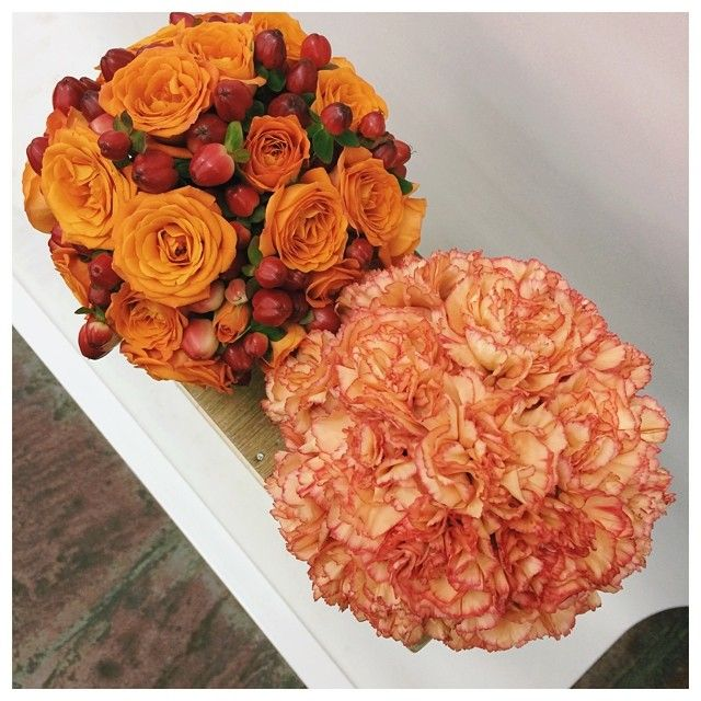 Shades of oranges featuring roses, hypericum, and carnations