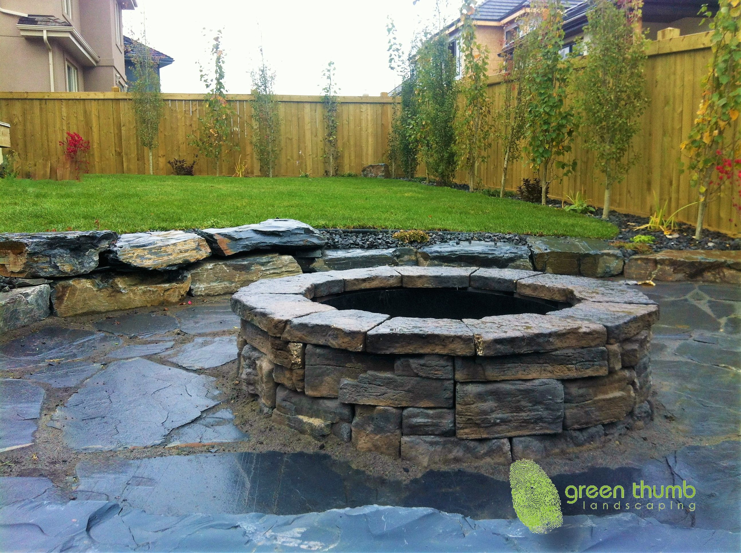 This yard was on a steep slope so we made a sunken fire pit area with the boulder retaining wall ...