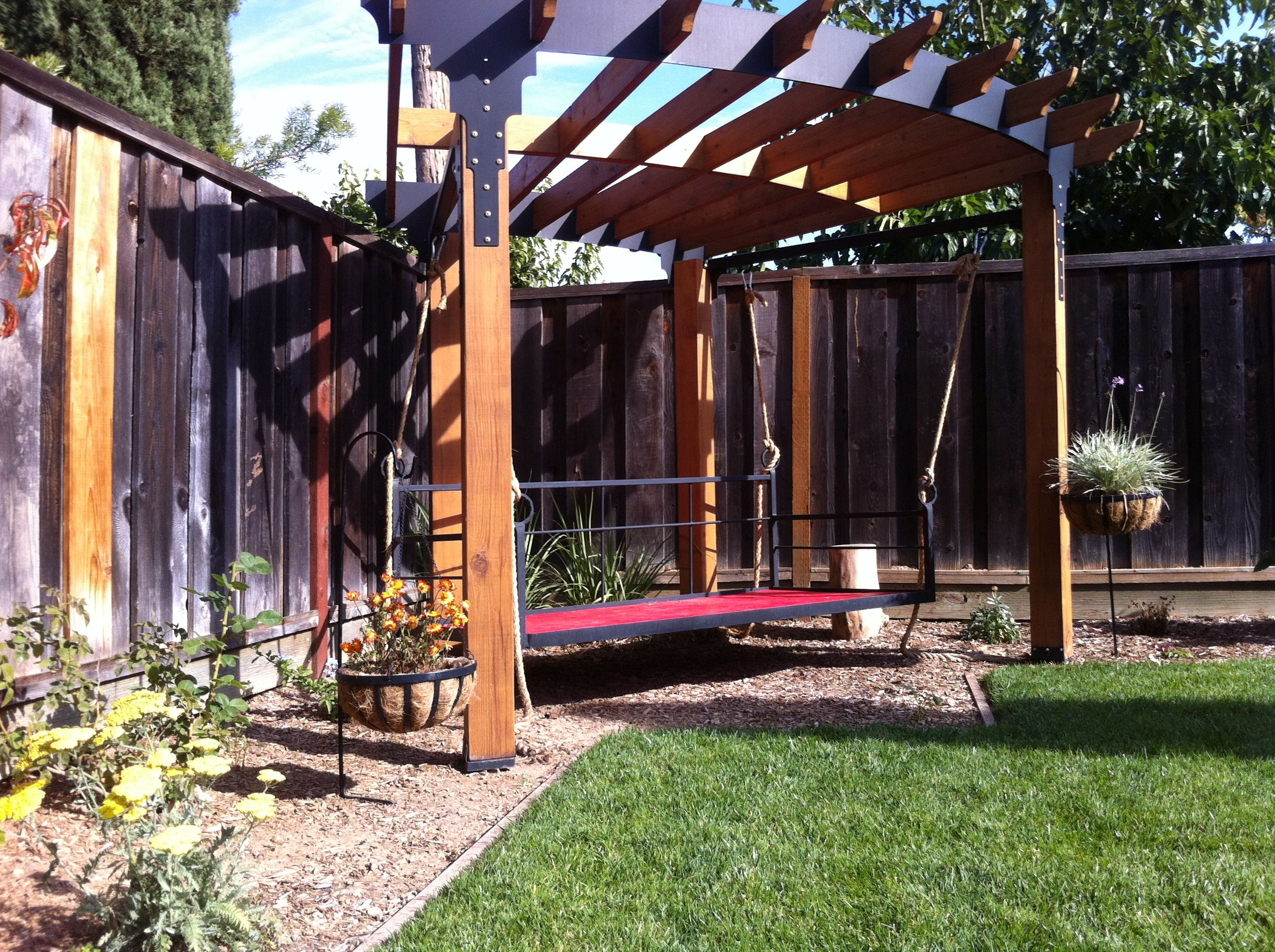 trapezoid gazebo pergola with a hanging day bed fits nicely in