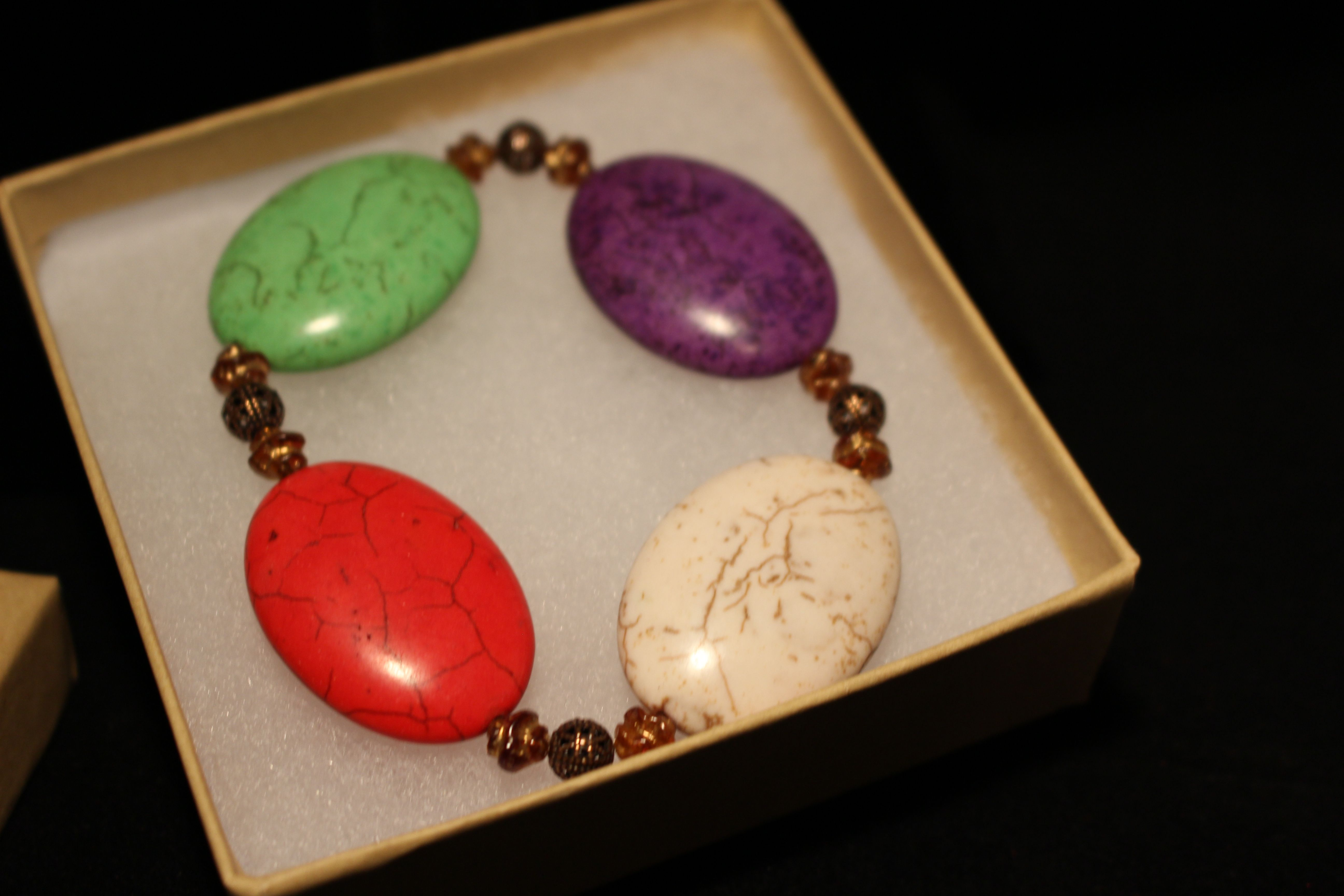 Ceramic multi-colored oval puff beads (34x24mm), acrylic honey/gold twist beads (6mm) with brass spacers.