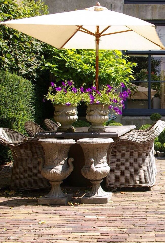 Beautiful Patio Space With Brick Pavers And Urns And Wicker Seating.