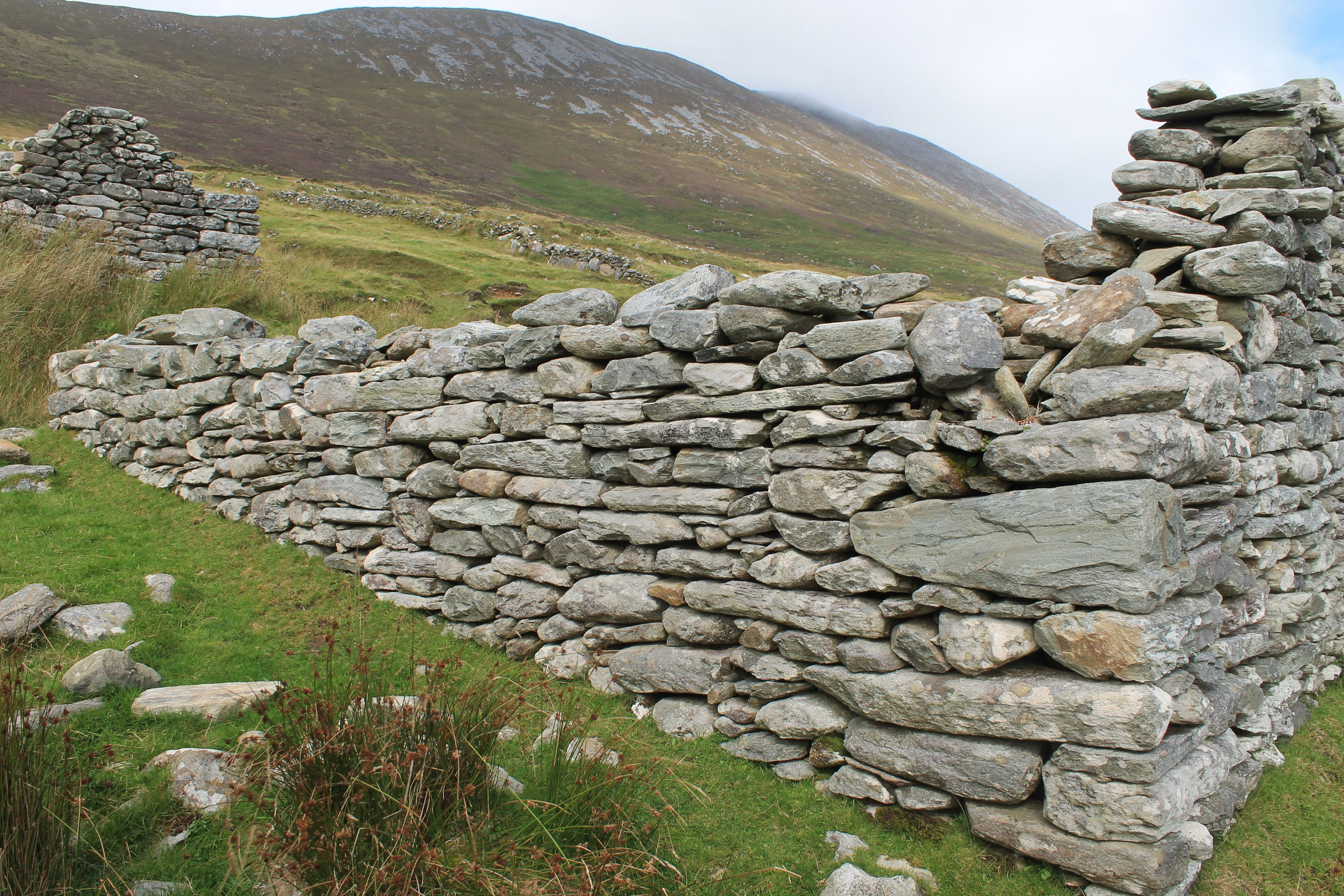 At the base of Slievemore mountain, on Achill Island, Ireland, lies the Deserted Village. There are approximately 80 ruined houses. https://en.wikipedia.org/wiki/Achill_Island#The_Deserted_Village & http://www.achilltourism.com/deserted.html
