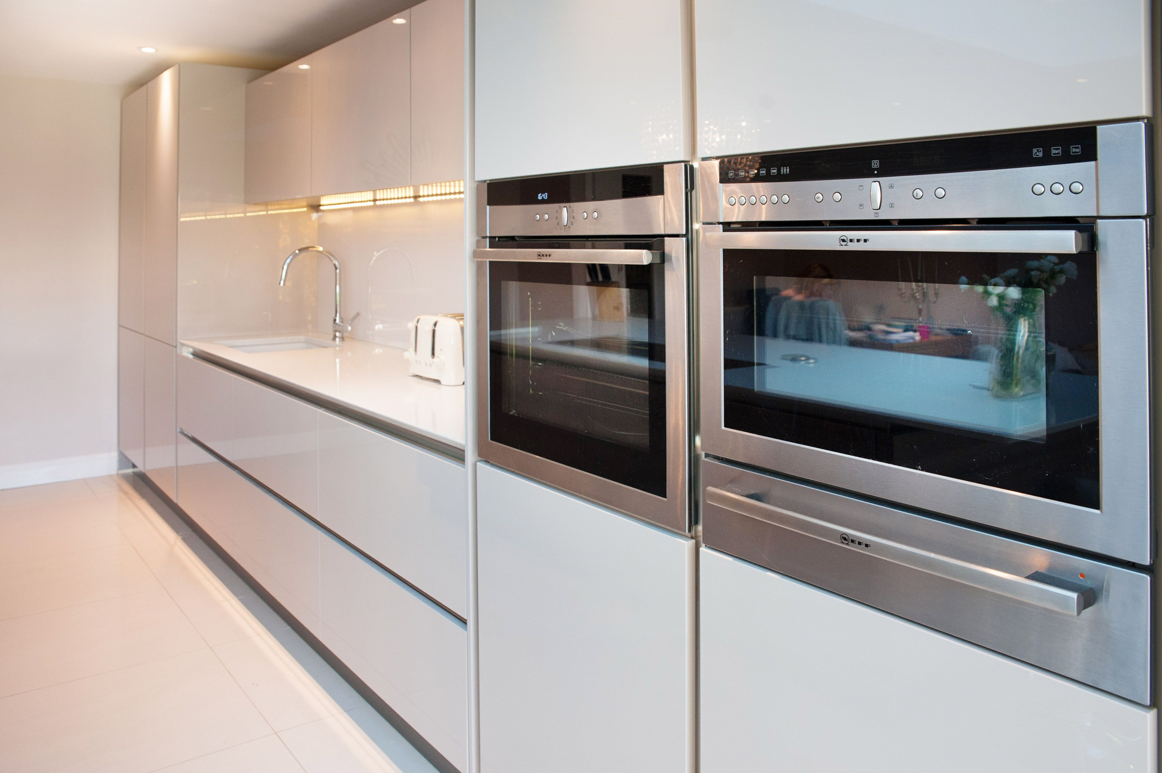 classic laser brilliant gloss cashmere true handleless and the large island is grey acacia work s german kitchen integrated oven open plan kitchen living room classic laser brilliant gloss cashmere