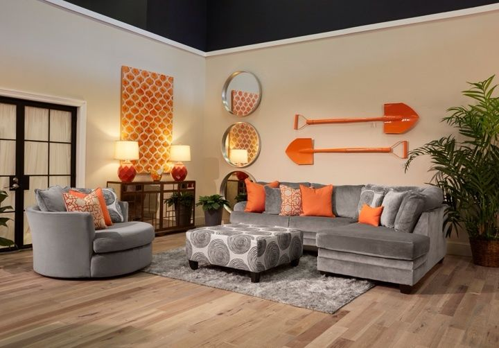 The application of orange and cool grey in this living room ...