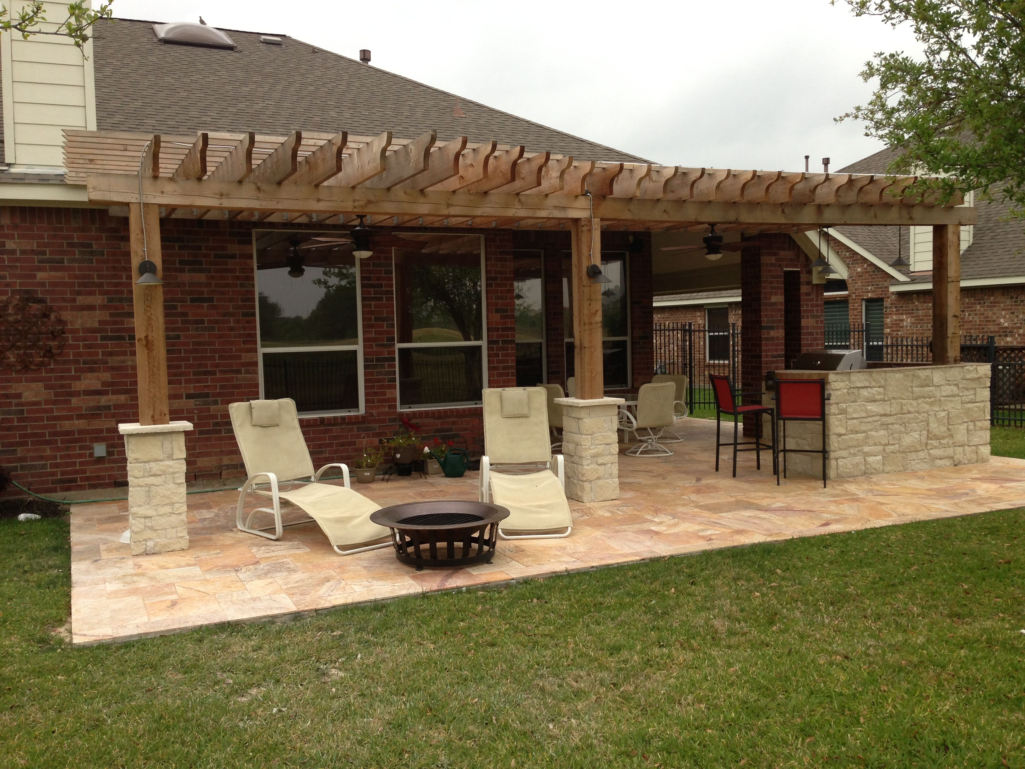 a wooden arbor addition with a fire pit area small outdoor kitchen