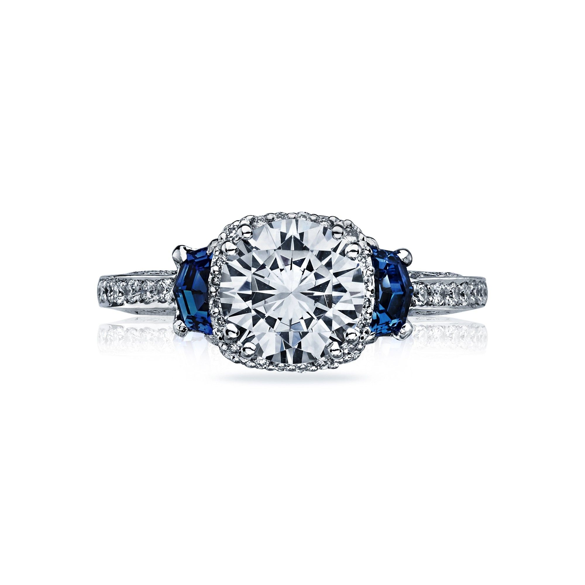 Tacori style no. 2628RDSP. A sweetly seductive style for the confident charmer. Architectural flair beautifies geometric cadillac-shaped sapphires. The depths of the blue sapphire set ablaze pave-set diamond detailing. A crown of intensifying diamonds around the center diamond make this ring incredibly special.