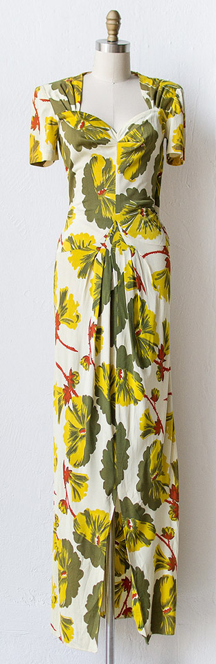 1940s bold and vibrant leaf print gown featuring short sleeves with light shoulder pads, a sweetheart neckline, and a fitted waist with ruching above the hips. There are seam pleat details at the waist that gives the maxi skirt dimension at the front center. There is a slit in the skirt at the front cener and button closures on the side seam. Via Adored Vintage.