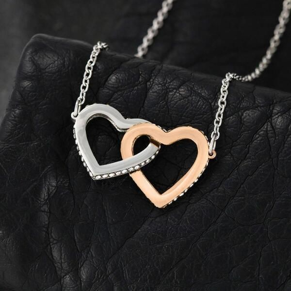 """Give your wife a thoughtful anniversary gift which will remind her of your love always. This design allows you to personalize your message making it even more special. Two hearts embellished with Cubic Zirconia stones, interlocked together as a symbol of never-ending love. Made with high quality polished surgical steel. Cable chain measures 18 inches with a 4 inch extension, and fastens with a lobster clasp. Pendant Dimensions:  • Height 0.6"""" (1.5cm) • Width 1.1"""" (2.7cm) • Adjustable cable chain"""