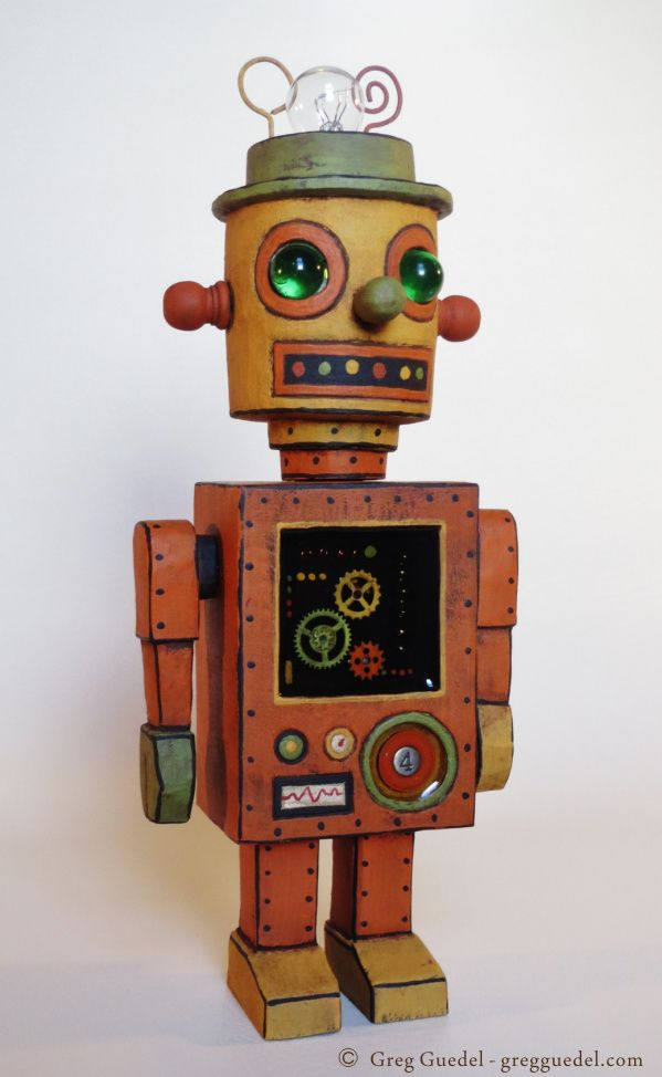 Robot wood carving by Greg Guedel. Inspired by vintage tin toys. Wood, marbles, metal gear, and clear poured resin.