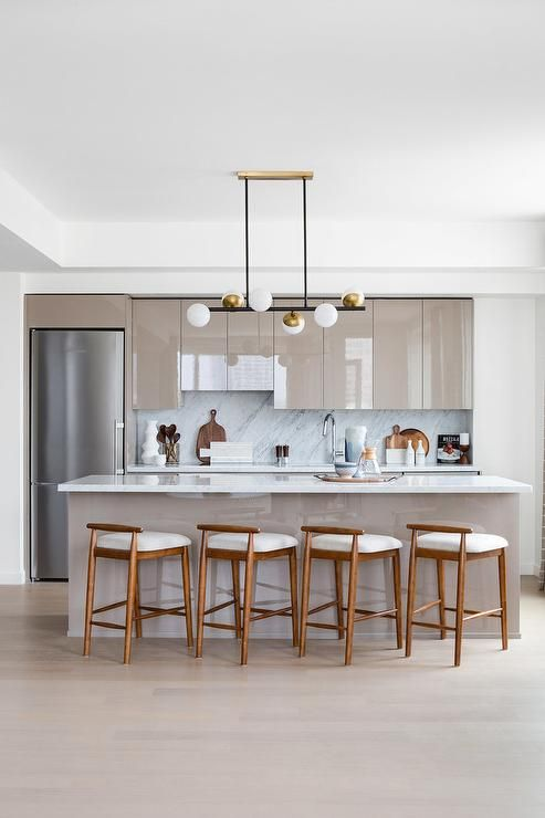 Four Low Back Wood Counter Stools Sit At A Glossy Taupe Island Accented With A Marble Countertop Illumina Modern Kitchen Counters Kitchen Layout Modern Kitchen